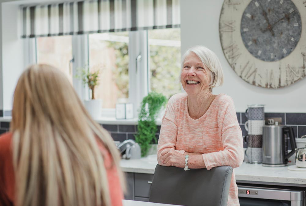 adults talking in kitchen about downsizing into senior apartments