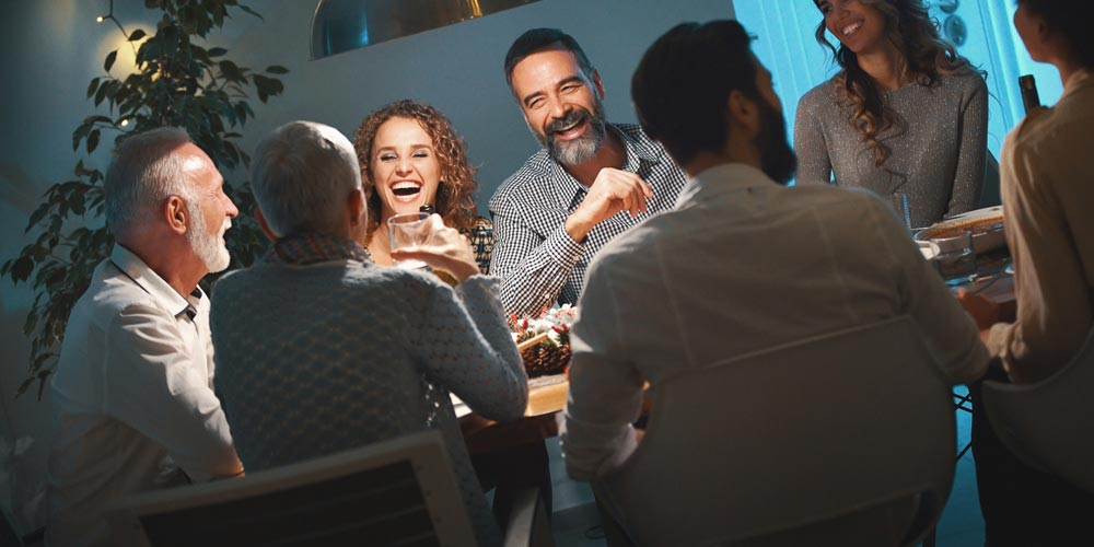 group of friends in senior housing laughing at dinner