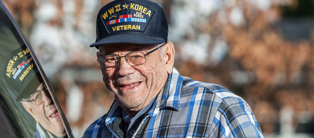 80 year old man smiling in world war two hat