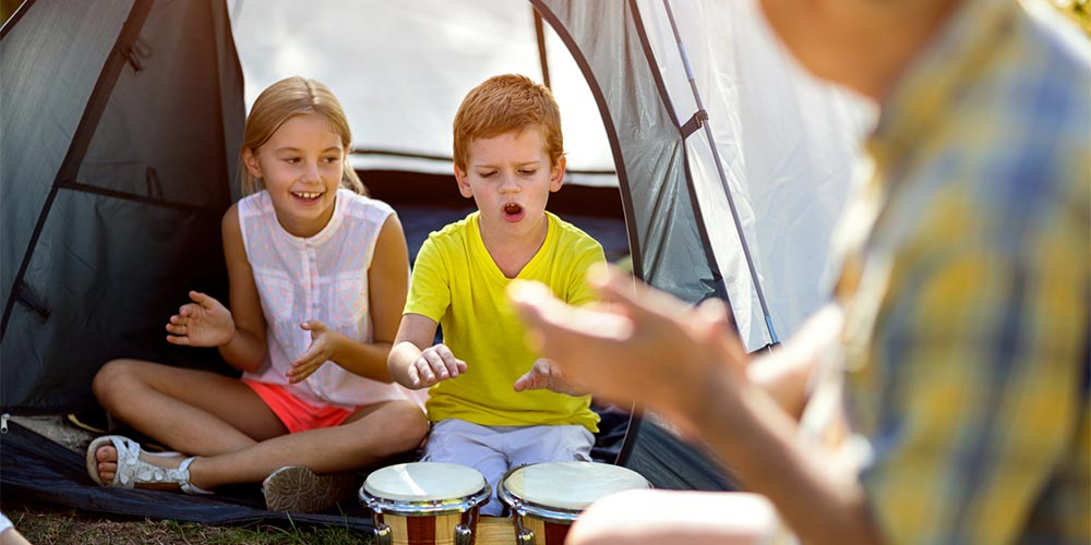 Grandfather with grandkids camping playing bongos