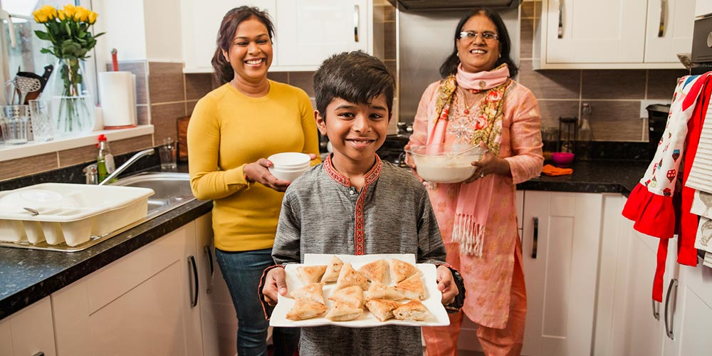Indian fanily cooking samosas in the kitchen