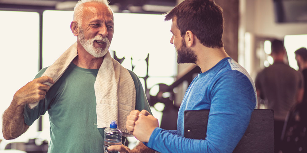 older male adult working with personal trainer in gym