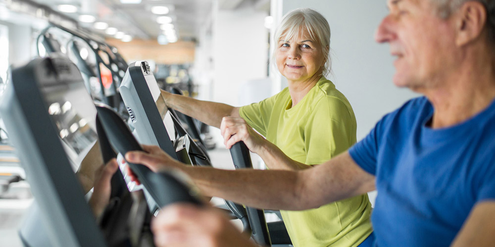 two active older adults on treadmills