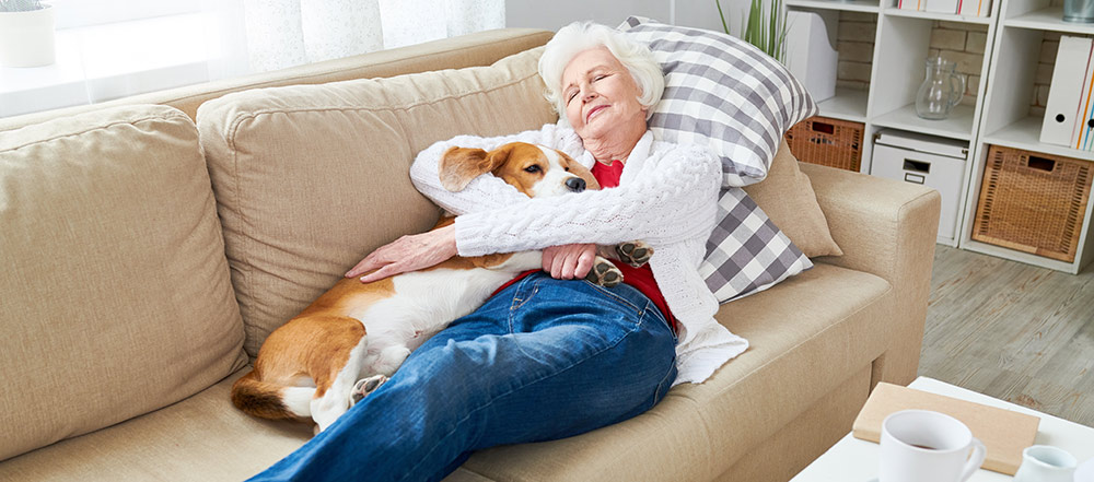 woman snuggling with corgi in her senior apartment